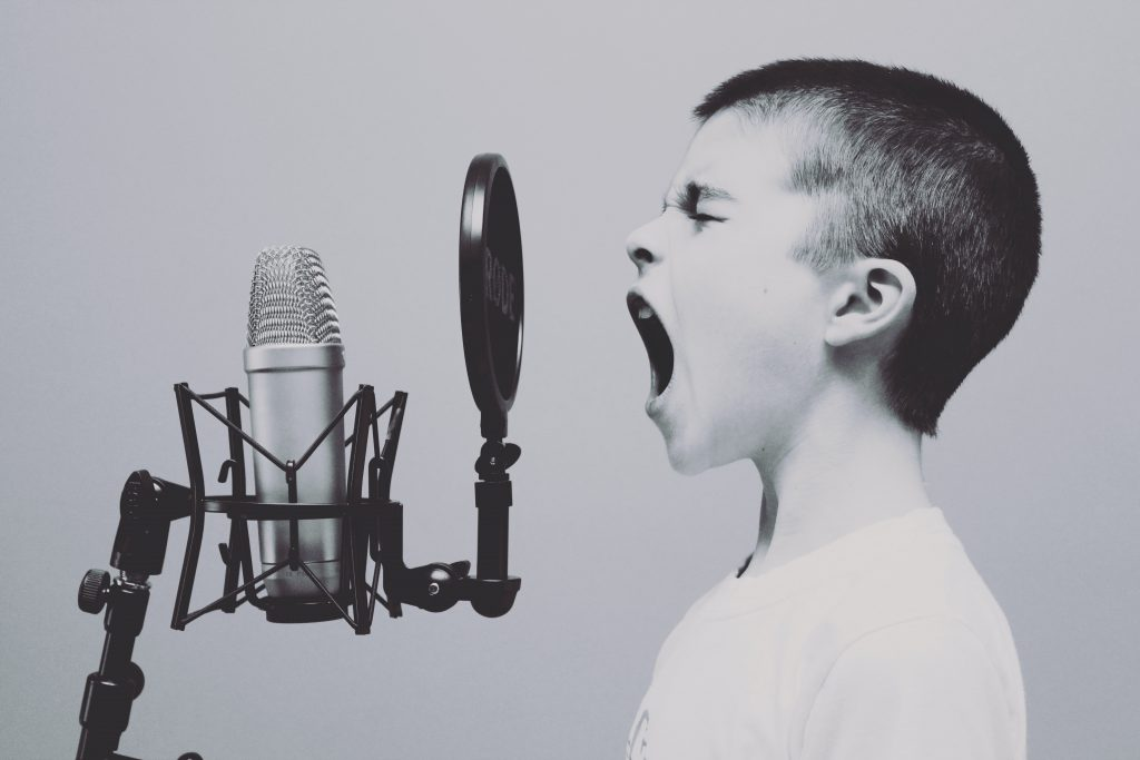 Image of kid screaming to a microphone